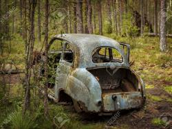 94282796-abandoned-old-car-wreck-in-the-forest-